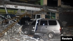 Debris from a building of Surigao State College and Technology is seen on a car after an earthquake hit Surigao city, southern Philippines, Feb. 10, 2017.