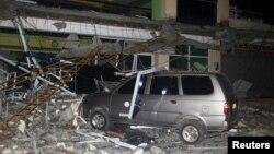 Reruntuhan gedung di Perguruan Tinggi dan Teknologi Negeri Surigao tampak menimpa sebuah mobil setelah gempa melanda kota Surigao (10/2). Surigao, Filipina Selatan. (foto: REUTERS/Roel Catoto-Mindanews)