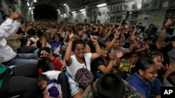 Typhoon survivors who were evacuated from Tacloban city cheer while seated onboard a U.S. military C-17 aircraft after they landed at Manila Airport, Nov. 17, 2013, in Manila, Philippines.