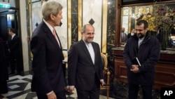 在奥地利维也纳国际谈判前,美国国务卿克里(左)和伊朗外长扎里夫的助手在酒店会面。(2015年10月29日)