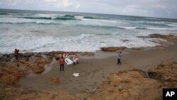 Des éléments de la Croix Rouge ramassent le corps d'un migrant mort par noyade lors d'une tentative de traversée pour l'Europe, à Khoms, Libye, 25 octobre 2015.
