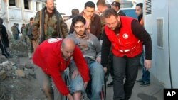 Syrian Arab Red Crescent members in red uniforms help evacuate injured man on a bus out of the battleground city of Homs. This photo was released by the official Syrian news agency.