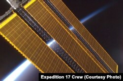 Earth's horizon and the International Space Station's solar panel array, Aug. 2008.