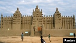 Wasu matsa suke wasan kwallo a gaban wani ksaitaccen Masallaci a Jenne na Mali.