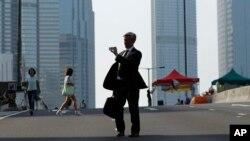 10月6日一位上班人士走在仍有抗議者搭建路障的街道上。