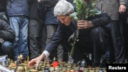 El secretario de Estado de EE.UU., John Kerry, prende una vela en el parque Independence Square, en Kiev, donde murieron decenas de protestantes en las marchas antigubernamentales de las semanas pasadas.