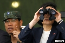 FILE - Taiwan's President Tsai Ing-wen looks through a pair of binoculars during anti-invasion drill, simulating the China's People's Liberation Army invading the island, in Taoyuan, Taiwan, Oct. 9, 2018.
