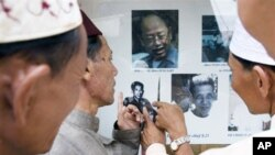 Khmer Islam men pointing at photos of former Khmer Rouge leaders, in Tuol Sleng museum.