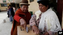 FILE - A woman is seen casting her ballot at a polling station during a referendum on allowing President Evo Morales to run for a fourth term in 2019, in El Alto, Bolivia, Feb. 21, 2016.