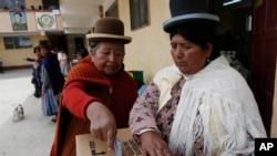 ແມ່ຍິງຊົນເຜົ່າ Aymara ຄົນໜຶ່ງປ່ອນບັດຄະແນນສຽງທີ່ສູນ ການເລືອກຕັ້ງ ໃນລະຫວ່າງການລົງປະຊາມະຕິແກ້ໄຂລັດ ຖະທຳມູນ ທີ່ເມືອງ El Alto, ປະເທດ ໂບລີເວຍ. 21 ກຸມພາ, 2016.