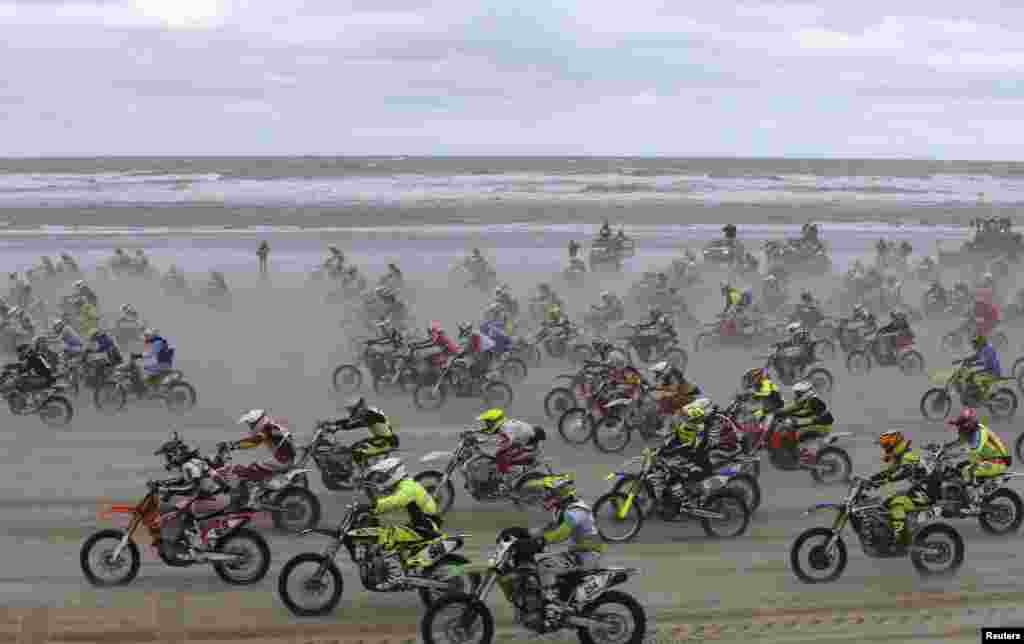"""Bikers start off on the sand as they take part in the """"Enduropale"""" motorcycle endurance race on the beach of Le Touquet, northern France."""