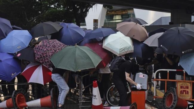 形成路障阻挡香港道路的抗议者躲在遮阳伞后面。(美联社2019年10月4日)