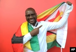 FILE - Pastor Evan Mawarire poses for a photo with the Zimbabwean flag wrapped around him, in Harare, Zimbabwe, May. 3, 2016. Mawarire rose to prominence last April when he posted a Facebook video of himself wrapped in a Zimbabwean flag, criticizing the state of affairs in the country.