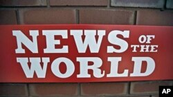 A News of the World sign is seen by an entrance to a News International building in London, Wednesday, July 6, 2011