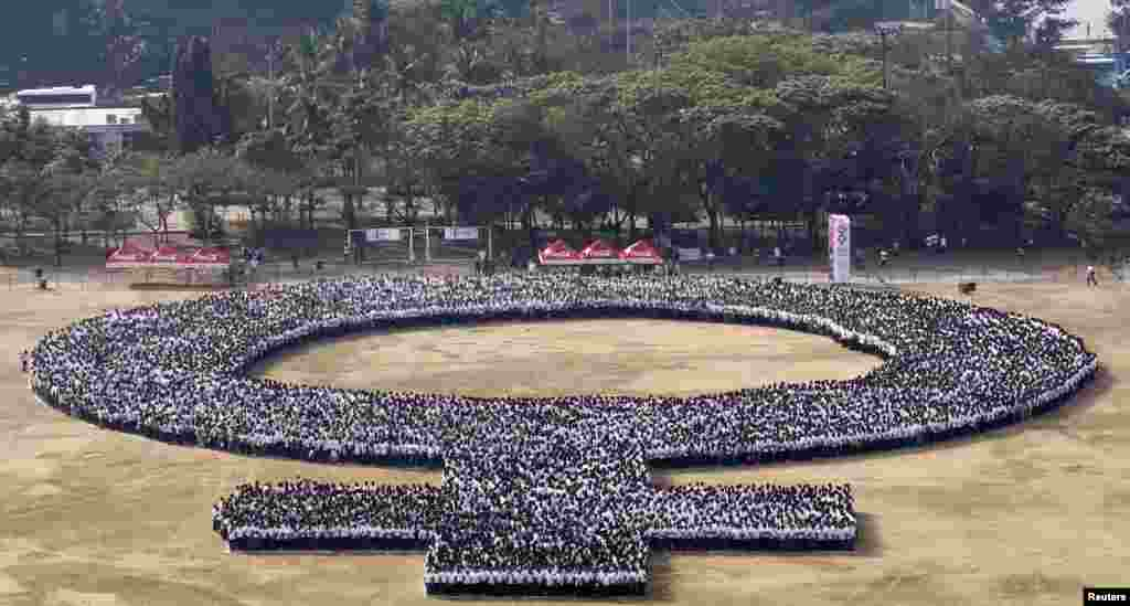 Participants form a female symbol as part of celebrations for International Women's Day in Manila, Philippines.