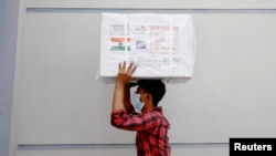 A worker carries a package of Oxford-Astrazeneca COVID-19 vaccines that arrived from India as a gift to Bangladesh, in Dhaka, Bangladesh January 21, 2021.