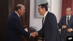 Greek Prime Minister Alexis Tsipras, center, welcomes U.S. Commerce Secretary Wilbur Ross, left, during their meeting in the northern port city of Thessaloniki, Greece, Sept. 7, 2018.