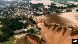 Rescuers rush to help people trapped in their homes in the town of Erftstadt, southwest of Cologne. Aerial pictures, like this one provided by the Cologne district government, show what appears to be a massive sinkhole.