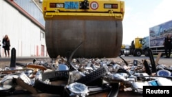 Una aplanadora es utilizada para destruir cientos de relojes pirateados.