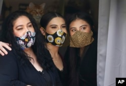 In this Monday, May 18, 2020, photo, Anissa Archuleta, center, sits at a window with her sister Alexis Archuleta, right, and her mother, Jaime Ortega, at their home in Midvale, Utah. The women all tested negative, but received daily calls from health investigators.