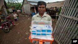 FILE - А malaria worker is seen carrying a traditional medicine kit in a village near Pailin, Cambodia, Aug. 29, 2009. Scientists have found that conventional kits could be replaced with artemisinin, a cheap but highly effective anti-malaria drug.