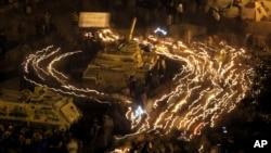 Des manifestants anti-gouvernement entourent une auto-blindée de l'armée égyptienne, au Caire, Egypte, 9 février 2011