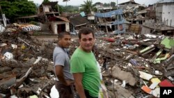 FILE - Neighbors watch a bulldozer demolish earthquake-damaged homes in Pedernales, Ecuador, Saturday, April 23, 2016.