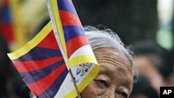 An exile Tibetan carries a Tibetan flag during a protest gathering in the Tsuglakhang temple in Dharmsala, India, Apr 24 2011