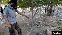 Một nhà hoạt động đeo mặt nạ tại hiện trường sau một vụ tấn công bị nghi là vũ khí hóa học tại Zamalka, Damascus, ngày 22/8/2013.