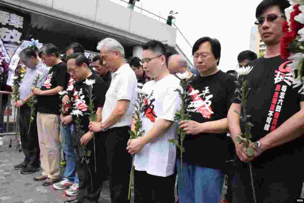 參與支聯會清明獻花活動的人士,手持白菊花為中國民運及六四事件死難者默哀。(美國之音湯惠芸攝)