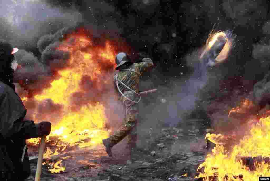 Một người biểu tình ủng hộ châu Âu ném một lốp xe đang cháy trong cuộc đụng độ với cảnh sát chống bạo động ở Kyiv. Liên minh châu Âu đe dọa sẽ có hành động đối với Ukraina về việc nước này xử lý những cuộc biểu tình chống chính phủ sau khi ba người thiệt mạng trong những cuộc đụng độ bạo lực ở thủ đô.