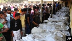 Bangladeshi people identify the bodies of their relatives died in a fire at a garment factory in the Savar neighborhood in Dhaka, Bangladesh, November 25, 2012.