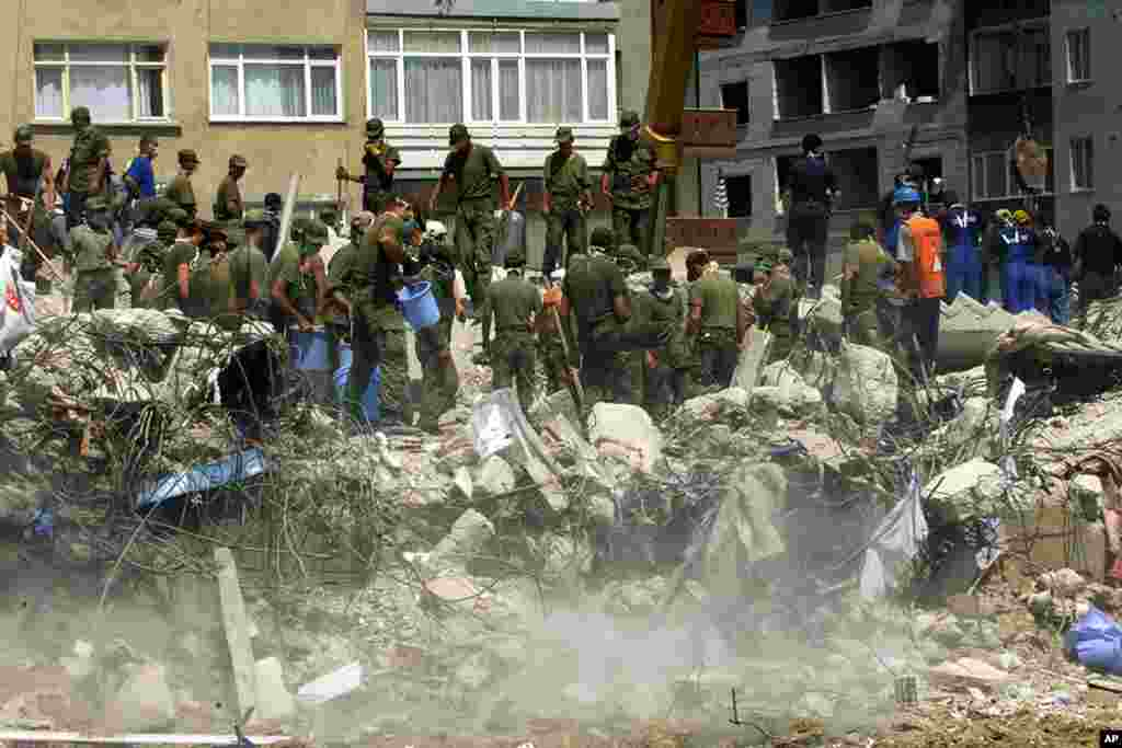 Turkish 3rd Army Corps soldiers attempt to lift rubble from the wreckage of a five-story apartment building in the Avcilar downtown district of Istanbul, August 20, 1999. (Reuters)