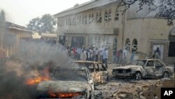 A car burns at the scene of a bomb explosion at St. Theresa Catholic Church at Madalla, Suleja, just outside Nigeria's capital Abuja, December 25, 2011.