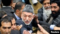 Presiden Afghanistan Hamid Karzai saat meninggalkan pertemuan hari terakhir Loya Jirga. (Reuters/Omar Sobhani)