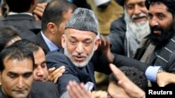 Afghan President Hamid Karzai leaves after the last day of the Loya Jirga, in Kabul, November 24, 2013.