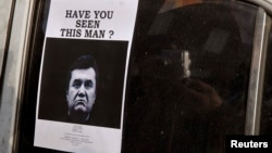 """FILE -- A man takes photos of a """"Wanted"""" notice, of fugitive Ukrainian President Victor Yanukovich, plastered on the window of a car used as barricade near Kyiv's Independent Square."""