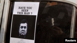 "A man takes photos of a ""Wanted"" notice, of fugitive Ukrainian President Victor Yanukovich, plastered on the window of a car used as barricade near Kiev's Independent Square February 24, 2014"
