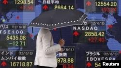 Una mujer se cubre de la lluvia mientras pasa frente al monitor del promedio Nikkei en Japón. Todavía no está claro las repercusiones de que Moody´s haya rebajado las calificaciones a 15 bancos a nivel mundial.