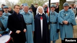 French President Emmanuel Macron poses with history enthusiasts, dressed with vintage army uniforms as Poilu (French World War I soldiers), after a ceremony at the Memorial to the Battle of Morhange, Eastern France, Nov. 5, 2018.