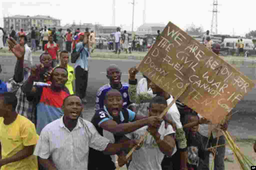 Angry youths protest with a placard 'We are ready for civil war if the fuel price cannot come down' on the third day of nation wide strike following the removal of a fuel subsidy by the government in Lagos, Nigeria, Wednesday, Jan. 11, 2012. Nigeria;s g