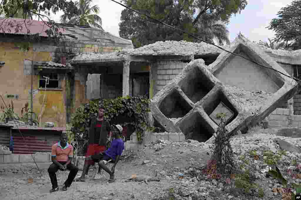 People sit outside a house that was destroyed by the January 2010 earthquake in Port au Prince, January 3, 2012. (Reuters)