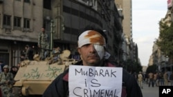 A wounded demonstrator carries a poster in Cairo, Egypt, Monday Jan. 31, 2011