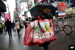 FILE - A woman walks through Times Square with holiday shopping bags, Dec. 2, 2015, in New York.