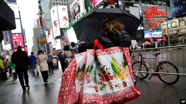 Woman walks through Times Square with holiday shopping bags, New York, Dec. 2, 2015.