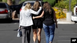 Kris Delarosby, right, and Colleen Anderson, left, hold Charleen Jochim as they walk toward a hospital in search of information about a missing friend, Steven Berger of Minnesota, Oct. 3, 2017, in Las Vegas. The parents of Berger, who had been missing after the mass shooting in Las Vegas, said they had been notified Tuesday afternoon that he was killed in the attack.
