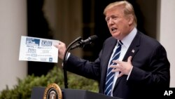 President Donald Trump holds up a piece of paper having to do with the Mueller Report as he speaks in the Rose Garden at the White House, May 22, 2019.