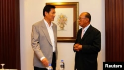 Secretary-General of Thailand's National Security Council Paradorn Pattanathabutr (L) speaks to Chairman of the Advisory Council for Peace Building in the Southern Border Provinces Aziz Benhawan, at a hotel in Kuala Lumpur, Mar. 28, 2013.
