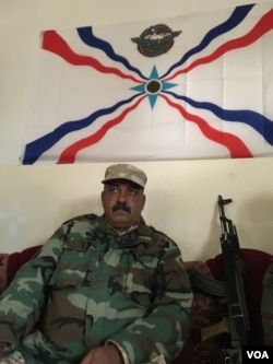 Dwekh Nawsha Col Sameer Oraha sits under the Assyrian Patriotic Party flag, his weapon propped up next to him. (S. Behn/VOA)