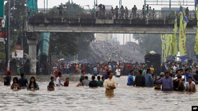 Ribuan warga Jakarta terpaksa mengungsi melalui jalanan yang tergenang banjir, Rabu (16/1). (AP Photo/Achmad Ibrahim)